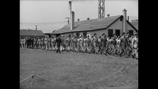 """car entering gates to camp. sign """"rnaf training camp little norway"""" cadets w/ rifles at attention vs cadets marching through camp. - 追放点の映像素材/bロール"""