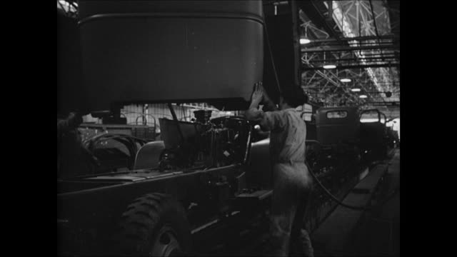Car factory INT MS Brazilian worker assembling vehicle frame on assembly line MS Worker bolting metal parts together EXT PAN HA WS Rows amp lines of...