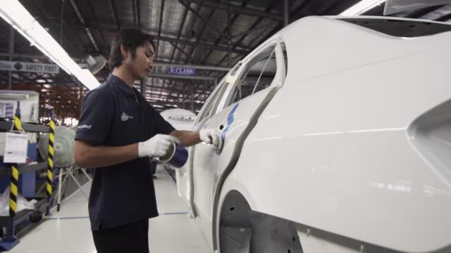ms car factory worker prepping car body for assembly / samut prakan, bang muang mai, thailand - nur junge männer stock-videos und b-roll-filmmaterial