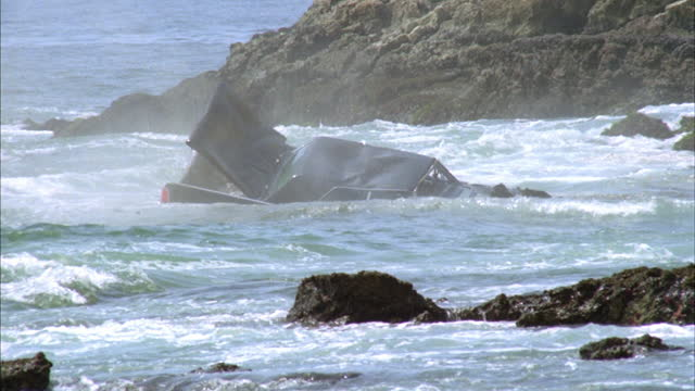 a car falls off a cliff into an ocean. - zerstört stock-videos und b-roll-filmmaterial