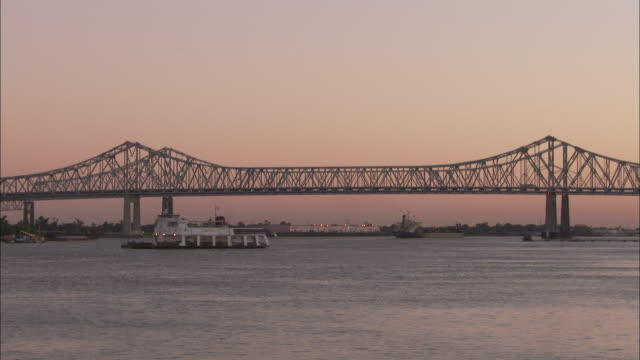 A car ferry moves across the Mississippi River near the Crescent City Connection Bridge. Available in HD