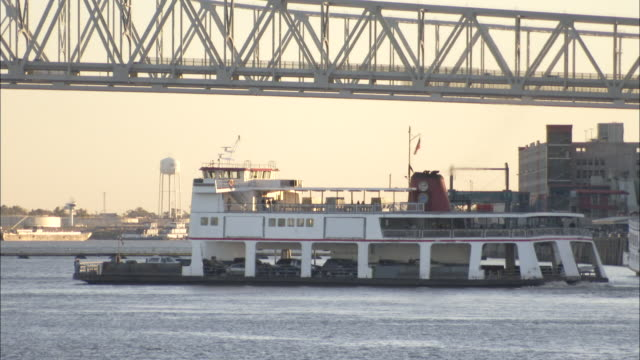 A car ferry moves into the centre of the Mississippi River. Available in HD