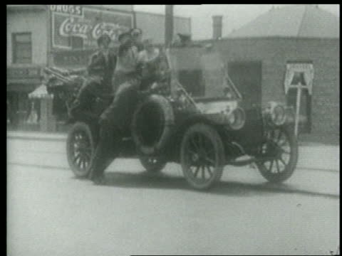 stockvideo's en b-roll-footage met b/w 1915 car filled with keystone kops + other pulling away leaving cop to fall on city street / short - 1915