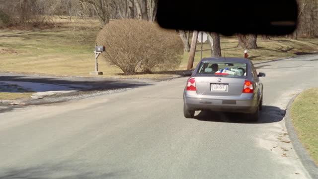ws car pov following car down wooded road/ port washington, new york - volkswagen stock-videos und b-roll-filmmaterial