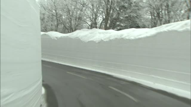 A car follows a van through a snowy corridor.
