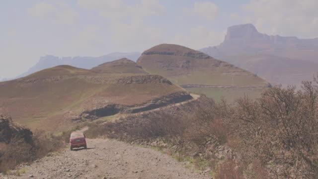car goes along a stone road towards the mountains - drakensberg mountain range stock videos & royalty-free footage