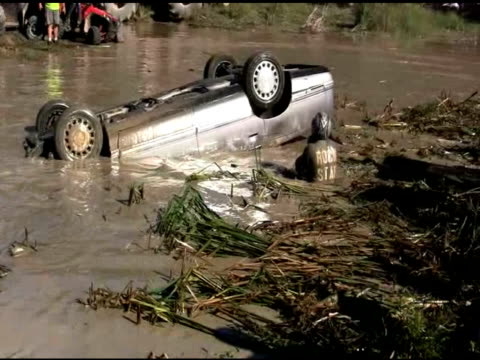 / car goes off ramp flies into air flips over and lands upside down in muddy swamp / rescuers race to get driver out of flipped car and crowd cheers... - ヒルビリー点の映像素材/bロール