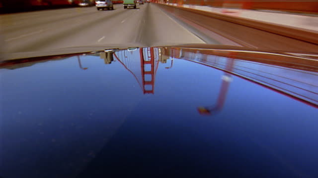 Car hood point of view driving over Golden Gate Bridge / time lapse traffic moving in reflections on hood and in background
