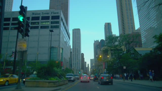 vidéos et rushes de slow motion car pov in traffic, through intersections, on michigan avenue in downtown chicago at twilight - chicago