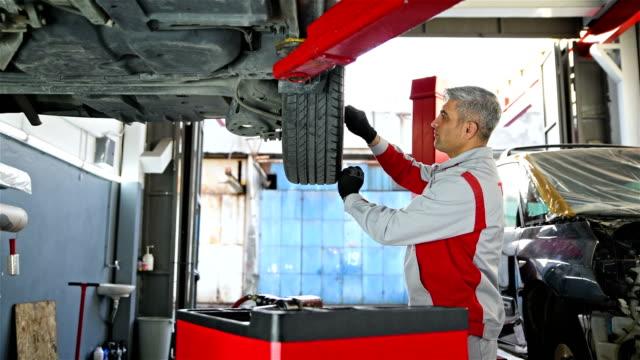 車の取り付けタイヤ - 自動車修理工場の車両部品 - 4k解像度 - 自動車部品点の映像素材/bロール