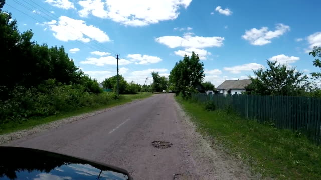Car is driving along a country road.