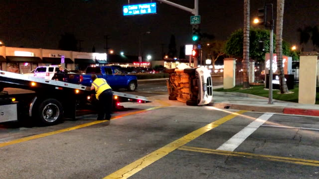 A car is rolled over by the towing company after a drunk driving accident