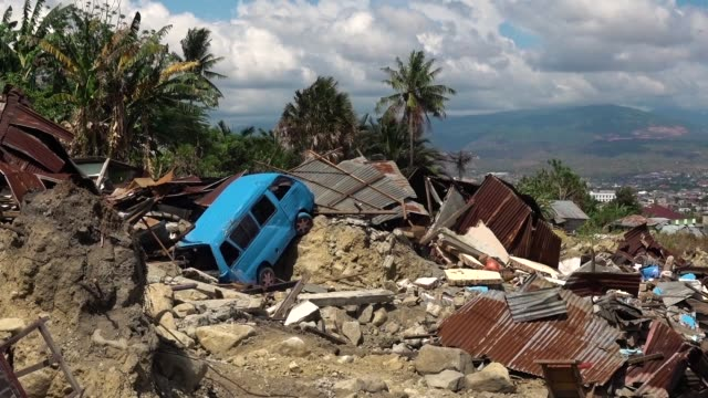 a car is seen in damaged area after being hit by tsunami in talise following the earthquake on october 12 2018 in palu indonesia indonesian officials... - indonesia earthquake stock videos & royalty-free footage
