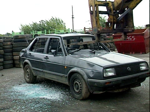 A car is taken by forklift truck for crushing at a recycling plant 2000
