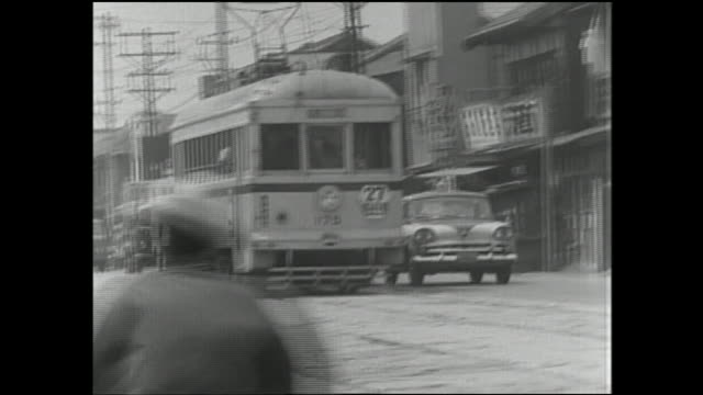 a car keeps pace with the toei streetcar as they speed along a city street. - 以前の点の映像素材/bロール