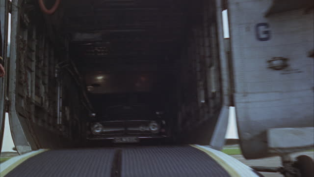 1966 REAR POV Car leaving cargo plane and driving on tarmac