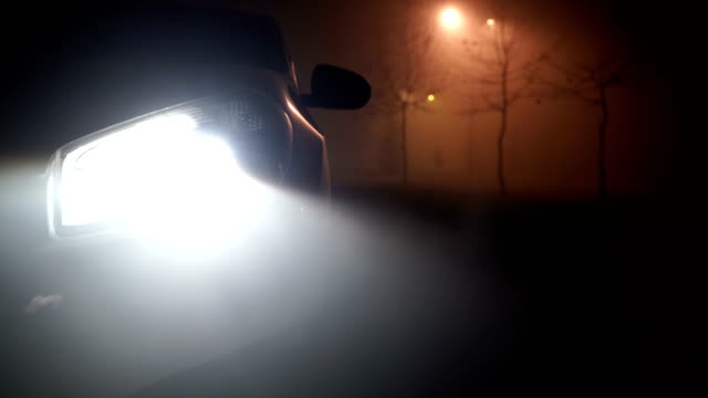 car lights beaming background.mysterious car in the woods, horror scene.close up - parking stock videos & royalty-free footage