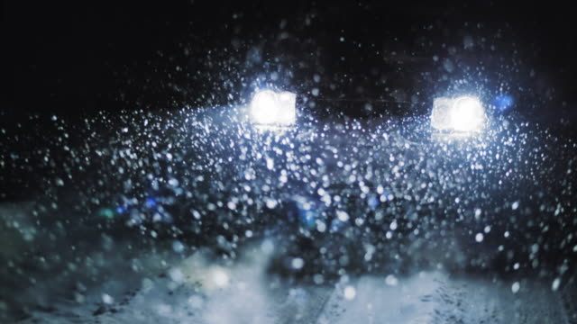 slo mo car lights in heavy snow at night - off road car stock videos and b-roll footage