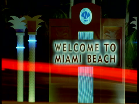 Car lights stream past Miami Beach sign