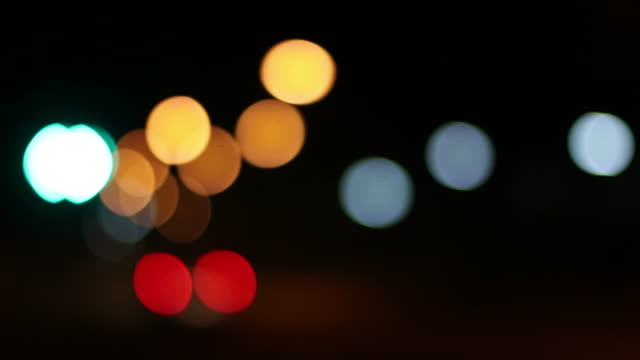 car lights with green lights - red lights blurred bokeh. - green light stock videos & royalty-free footage