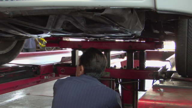 ms car lowers down as mechanic examining / los angeles, california, usa - 中年の男性だけ点の映像素材/bロール
