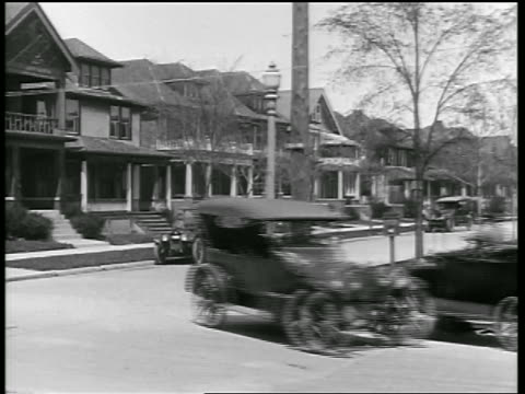vidéos et rushes de b/w 1919 car making sharp left turn on residential street + almost hitting other car / newsreel - 1910 1919