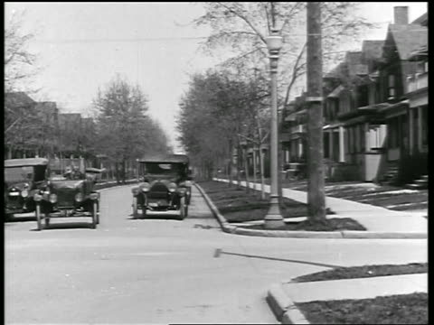 vidéos et rushes de b/w 1919 car making sharp left turn on residential street + cutting off other car / newsreel - 1910 1919