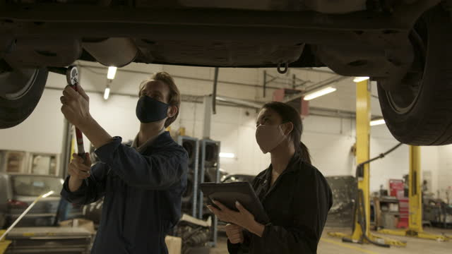 vídeos y material grabado en eventos de stock de car mechanic and trainee with protective face mask looking at car in auto repair workshop using digital tablet - garaje