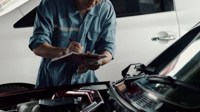 vidéos et rushes de mécanicien de voiture vérifiant la voiture pour des défauts et des erreurs - carnet