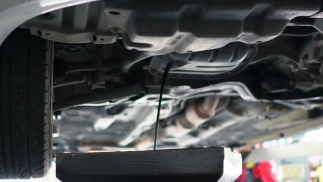 car mechanic draining oil from a car in slow motion - motor oil stock videos & royalty-free footage