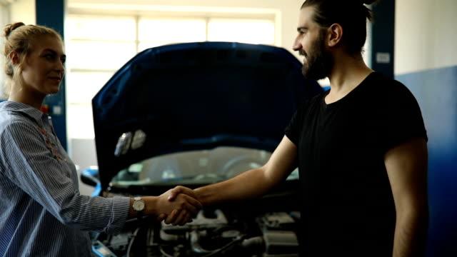 vidéos et rushes de mécanicien de client de mains - s'impliquer à fond