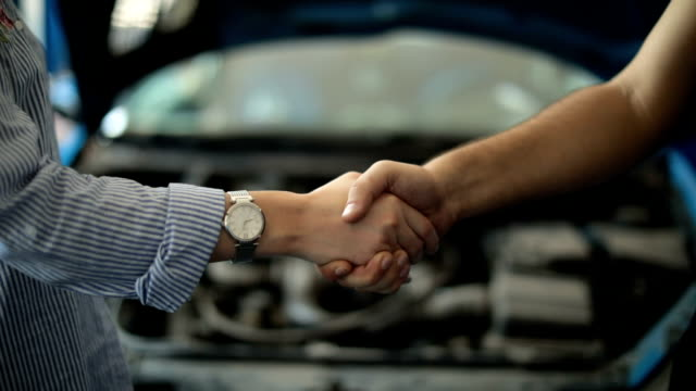 car mechanic handshakes customer - aggiustare video stock e b–roll
