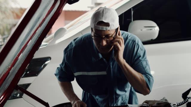 vídeos de stock, filmes e b-roll de conversa do mecânico do carro com o telefone esperto móvel - mecânico de carro