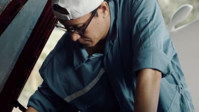 ガレージで働く車のメカニック - 日曜大工点の映像素材/bロール