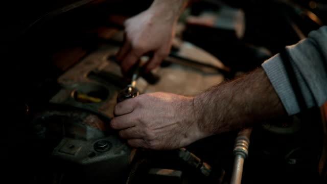 vidéos et rushes de garagiste travaillant dans le garage - qualité