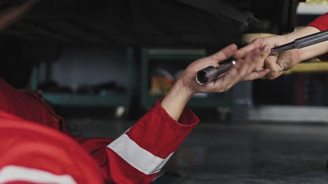 vidéos et rushes de mécanicien de voiture travaillant sur un moteur dans l'atelier de réparation automatique. - mécanicien