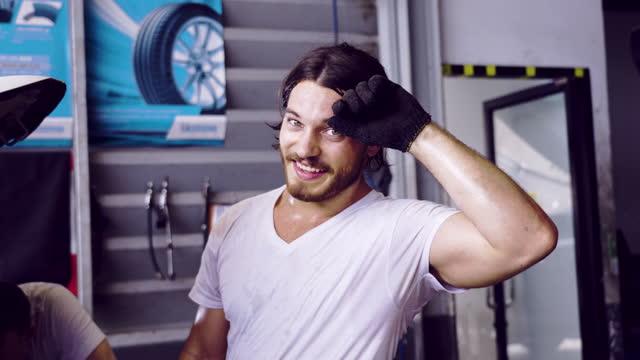 vidéos et rushes de mécanicien de voiture travaillant sur un moteur dans l'atelier de réparation automatique. jeune homme souriant et regardant camera.be fatigué. - sueur