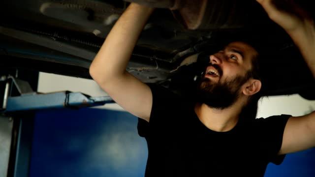 Car mechanic working under a vehicle at workshop