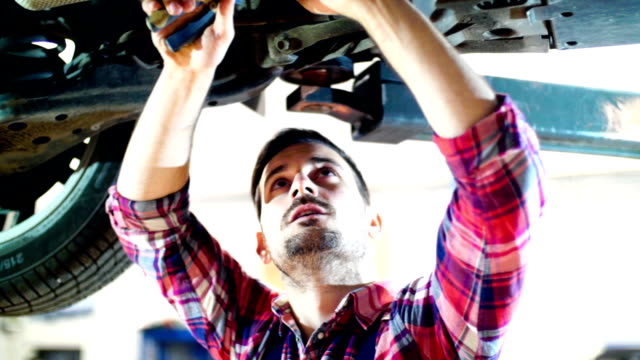 car mechanic working under a vehicle. - tow truck stock videos and b-roll footage