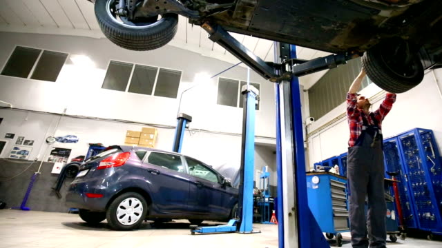 car mechanic working under a vehicle. - repair garage stock videos & royalty-free footage