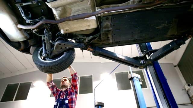 Bilmekaniker som arbetar under ett fordon.