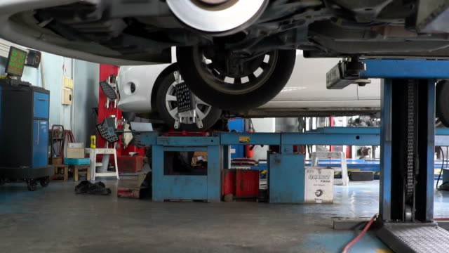 vidéos et rushes de garagiste travailler sous un véhicule - auto discipline
