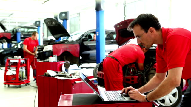 Car mechanics in workshop.