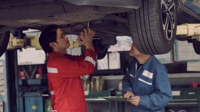 自動車修理工場でエンジンに取り組む自動車整備士。 - resting点の映像素材/bロール
