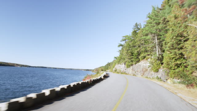 Car mounted to car as it drives on Sergeants Drive on MT Desert Island Maine in autumn fast