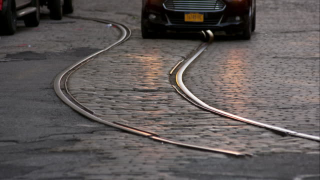 car moves along brick road with curved rail line in street - straßenbahnstrecke stock-videos und b-roll-filmmaterial
