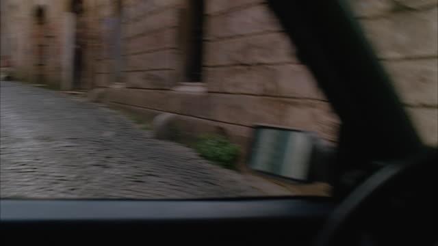ms pov car moving from cobblestone side streets in rome - スウィッシュパン点の映像素材/bロール