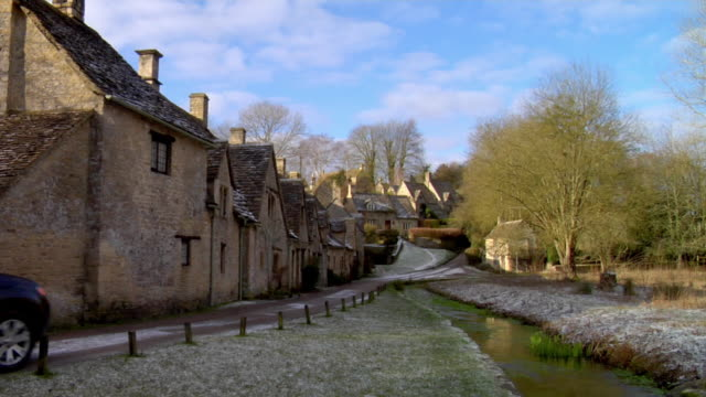 ws car moving on road by row of houses / arlington row, bibury, uk - landhaus stock-videos und b-roll-filmmaterial