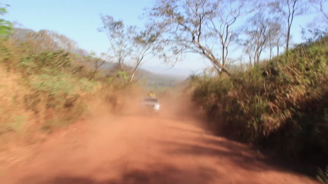 vídeos de stock, filmes e b-roll de ms pov car moving through dirt road / corumba, mato grosso do sul, brazil - estrada rural