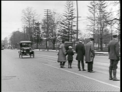 "B/W 1919 car nearly hitting people standing in street in ""Safety Zone"" / traffic cop reprimands him"